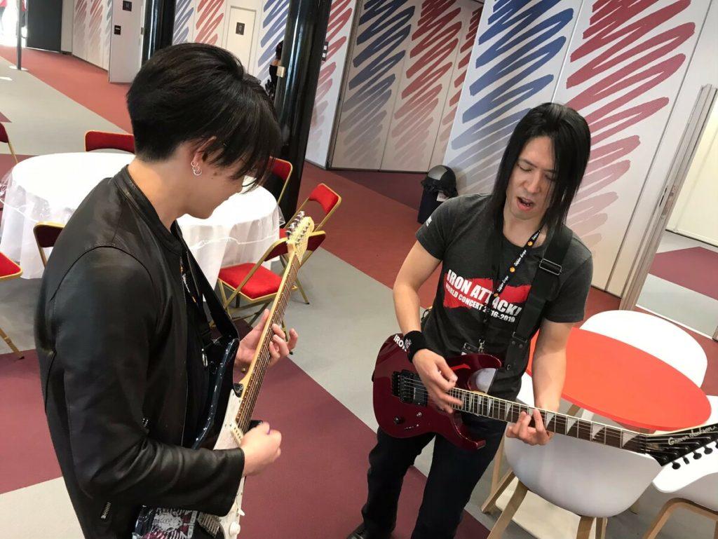 フランスでギターを弾くIRON-CHINOと龍5150